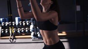 Aktive, junge brunette Frau, die Hocken beim Werfen eines Medizinballs oben gegen eine Wand in einer dunklen farbigen modernen Tu stock video
