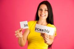 Aktive junge Frau, die den Text unmöglich über rosa backg auseinander reißt lizenzfreies stockfoto