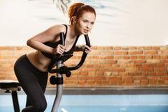 Aktive junge Frau, die zu Hause Übung auf Fahrrad tut Stockbild
