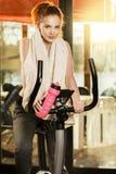 Aktive junge Frau, die zu Hause Übung auf Fahrrad tut Stockfotos