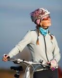 Aktive junge Frau mit ihrem Fahrrad Lizenzfreie Stockfotos