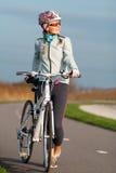 Aktive junge Frau mit ihrem Fahrrad Lizenzfreies Stockbild
