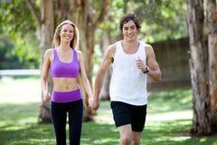 Aktive junge Paar-Holding-Hände im Park Stockbilder