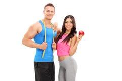 Aktive junge Paare, die mit einem Apfel aufwerfen Lizenzfreies Stockfoto