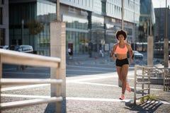 Aktive Junge tragen die Frau zur Schau, die draußen an einem sonnigen Tag läuft Stockfoto