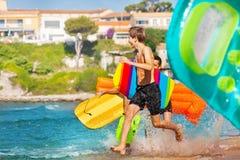 Aktive Jungen, die in das Meer mit Körperbrettern laufen lizenzfreie stockfotos
