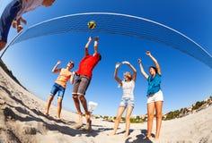 Aktive Jungen und Mädchen, die Volleyball auf Strand spielen stockfoto