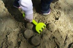 Aktive Kinderspiele des Sommers im Sandkasten stockbild