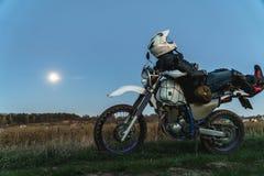 Aktive Lebensart, enduro Motorrad, ein Kerl betrachtet die Sterne nachts und den Mond, Einheit mit Natur, der Geist des Abenteuer stockfotografie