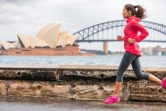 Aktive Lebensstilfrau des Läufersitzes, die auf Sydney Harbour durch den berühmten Touristenattraktionsmarkstein des Opernhauses  lizenzfreies stockfoto