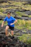 Aktive Mannspur, die auf vulkanischen Felsen läuft Stockbild