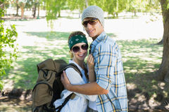 Aktive nette Paare, die auf einer Wanderung lächelnd an der Kamera sich umfassen Stockfoto