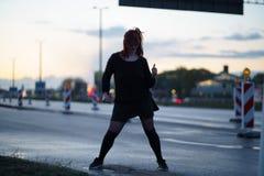 Aktive Reisendt?nzerfrau, die an einem Stra?enbaustandort zur Sonnenuntergangzeit mit den Autolichtern ?berschreiten durch das Tr lizenzfreies stockbild