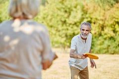 Aktive Senioren, die mit einem Frisbee spielen Lizenzfreie Stockfotos