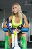 Aktive sexy Blondine in der Sportkleidung, die auf Sportausrüstung sitzt Gymnastik Trägt Nahrung zur Schau 2D chemische Strukture Stockbilder