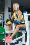 Aktive sexy Blondine in der Sportkleidung, die auf Sportausrüstung sitzt Gymnastik Trägt Nahrung zur Schau 2D chemische Strukture Stockfotografie