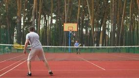 Aktive sportliche Männer, die Tennisspiel auf Hardcourt spielen stock footage