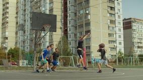 Aktive teeange Freunde, die draußen streetball spielen stock video footage