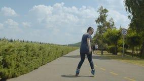 Aktive weibliche Rolle, die rückwärts in Park reitet stock video