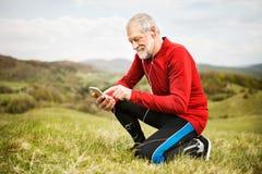 Aktiver älterer Läufer in der Natur mit intelligentem Telefon und Kopfhörern Stockfotos