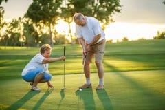Aktiver älterer Lebensstil, älteres Paar, das zusammen Golf spielt lizenzfreie stockfotos