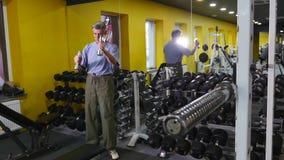 Aktiver alter Mann, der Übung mit Dummköpfen in einer Turnhalle tut stock video footage