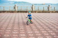 Aktiver blonder Kinderjunge, der Fahrrad im Park nahe dem Meer fährt Kleinkindkind, das Spaß am warmen Sommertag träumt und hat d Stockbilder