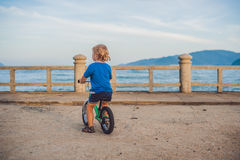 Aktiver blonder Kinderjunge, der Fahrrad im Park nahe dem Meer fährt Kleinkindkind, das Spaß am warmen Sommertag träumt und hat d Stockfoto