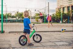 Aktiver blonder Kinderjunge, der Fahrrad im Park nahe dem Meer fährt Kleinkindkind, das Spaß am warmen Sommertag träumt und hat d Stockfotos