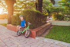 Aktiver blonder Kinderjunge, der Fahrrad im Park nahe dem Meer fährt Kleinkindkind, das Spaß am warmen Sommertag träumt und hat d Lizenzfreies Stockbild
