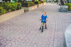 Aktiver blonder Kinderjunge, der Fahrrad im Park nahe dem Meer fährt Kleinkindkind, das Spaß am warmen Sommertag träumt und hat d Stockbild