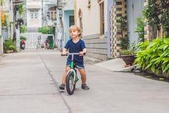 Aktiver blonder Kinderjunge, der Fahrrad n die Straße der Stadt fährt Kleinkindkind, das Spaß am warmen Sommertag träumt und hat  Lizenzfreies Stockfoto