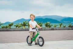 Aktiver blonder Kinderjunge und -fahrrad nahe dem Meer Kleinkindkind, das Spaß am warmen Sommertag träumt und hat draußen Spiele  Stockfoto