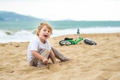Aktiver blonder Kinderjunge und -fahrrad nahe dem Meer Kleinkindkind, das Spaß am warmen Sommertag träumt und hat draußen Spiele  Stockbild