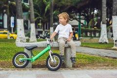 Aktiver blonder Kinderjunge und -fahrrad nahe dem Meer Kleinkindkind, das Spaß am warmen Sommertag träumt und hat draußen Spiele  Lizenzfreies Stockfoto