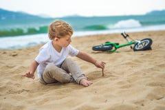 Aktiver blonder Kinderjunge und -fahrrad nahe dem Meer Kleinkindkind, das Spaß am warmen Sommertag träumt und hat draußen Spiele  Lizenzfreie Stockfotos