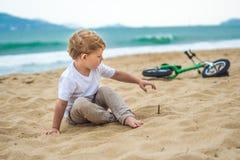 Aktiver blonder Kinderjunge und -fahrrad nahe dem Meer Kleinkindkind, das Spaß am warmen Sommertag träumt und hat draußen Spiele  Stockfotografie