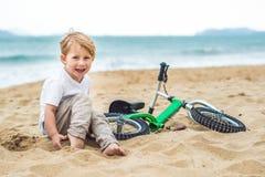 Aktiver blonder Kinderjunge und -fahrrad nahe dem Meer Kleinkindkind, das Spaß am warmen Sommertag träumt und hat draußen Spiele  Lizenzfreies Stockbild
