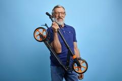 Aktiver hübscher alter Mann in der stilvollen zufälligen Kleidung wird Roller reiten stockfotos