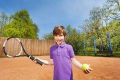 Aktiver Junge mit Schläger und Ball, der Tennis spielt Stockbild