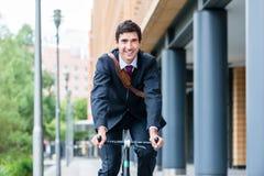Aktiver junger lächelnder Mann beim Fahren Gebrauchsfahrrads zu seinem wor Stockbilder