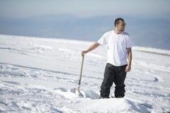 Aktiver junger Mann, der Schnee schaufelt Stockfoto