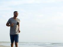 Aktiver junger Mann, der am Strand rüttelt Lizenzfreies Stockbild