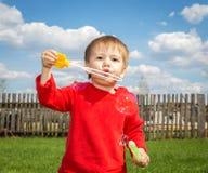 Aktiver kleiner Junge, der draußen mit Seifenblasen spielt stockbild