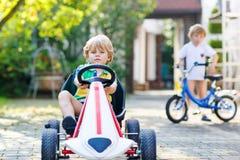Aktiver kleiner Junge, der Tretauto im Sommergarten fährt Lizenzfreie Stockfotos