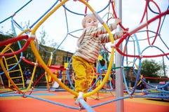 Aktiver Kleinkindjunge, der Spaß auf Spielplatz hat Lizenzfreie Stockfotografie