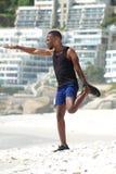 Aktiver Mann, der Muskeln am Strand ausdehnt Stockbild