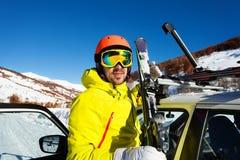 Aktiver Mann, der Skis von den Autodachschienen entlädt Stockbilder