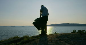 Aktiver Mann mit Rucksack kampierend am moutain durch das Meer bei Sonnenuntergang stock video footage