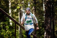 Aktiver Mannathlet, der an Hand in Wald laufen, ein Rucksack auf seinem Rückseite und Uhr Lizenzfreie Stockfotos
